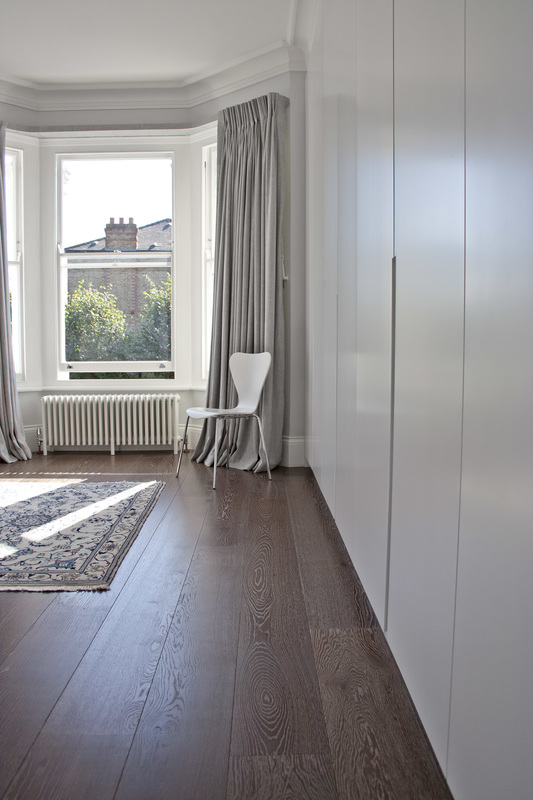 Bespoke full master bedroom white wardrobe with bevelled door pulls designed by Studio Fade